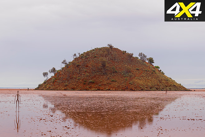 Conical island of red rock at the lake