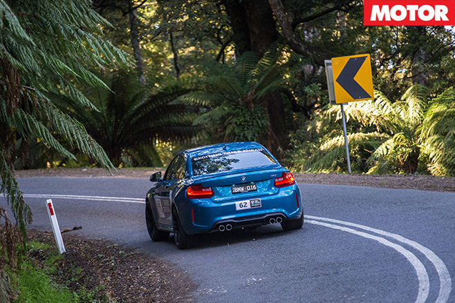 BMW M2 driving through forest