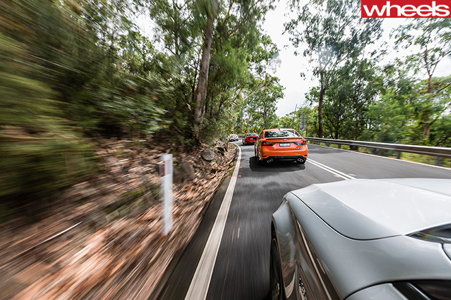 BMW-M3-vs -HSV-Clubsport -LSA-vs -Lexus -GS-F-vs -Mercedes -AMG-C63-S-rear -view -of -group -driving -around -corner