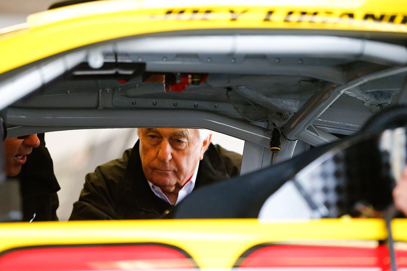 Roger Penske inspecting NASCAR vehicle