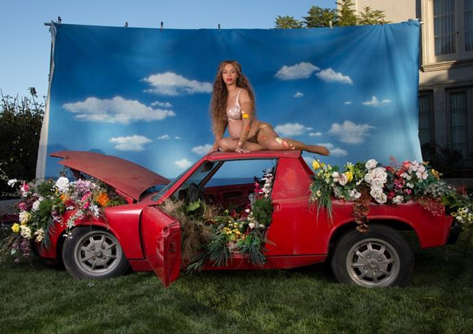 She also posed on top of a car full of flowers. Because, why not?
