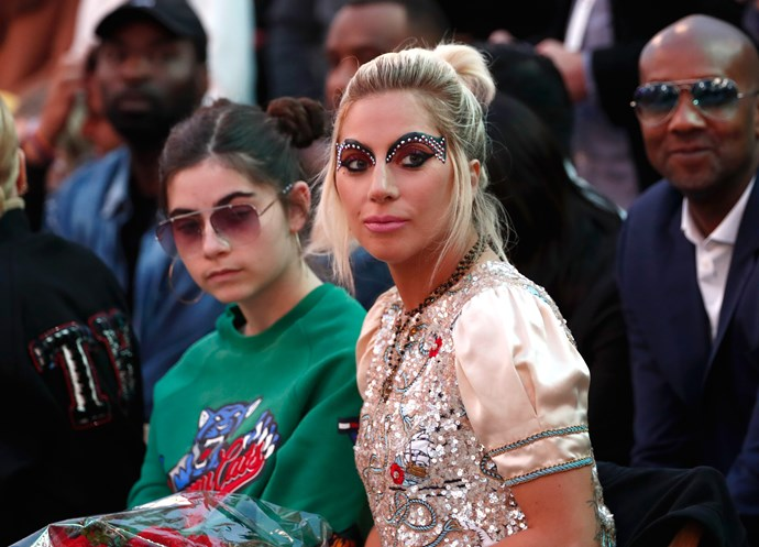Lady Gaga alongside what looks like Christian's daughter Bella at the Tommy Hilfiger fashion show on Wednesday night.