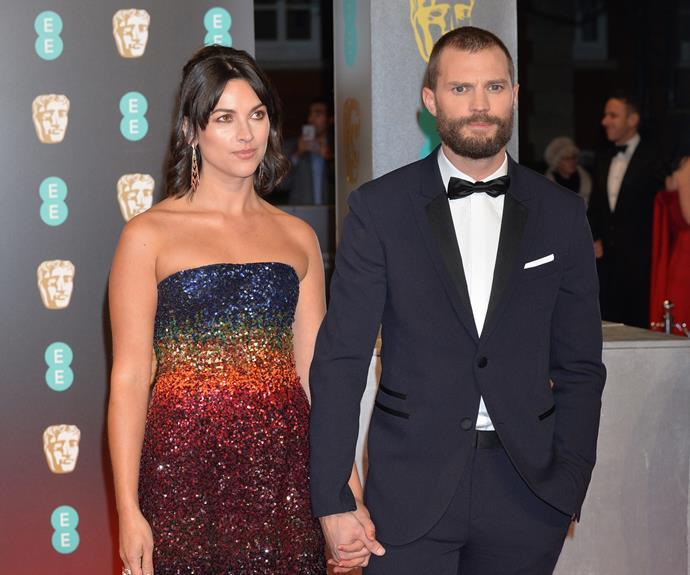 Why so serious? A pouty Jamie Dornan walks the red carpet with his wife Amelia Warner.
