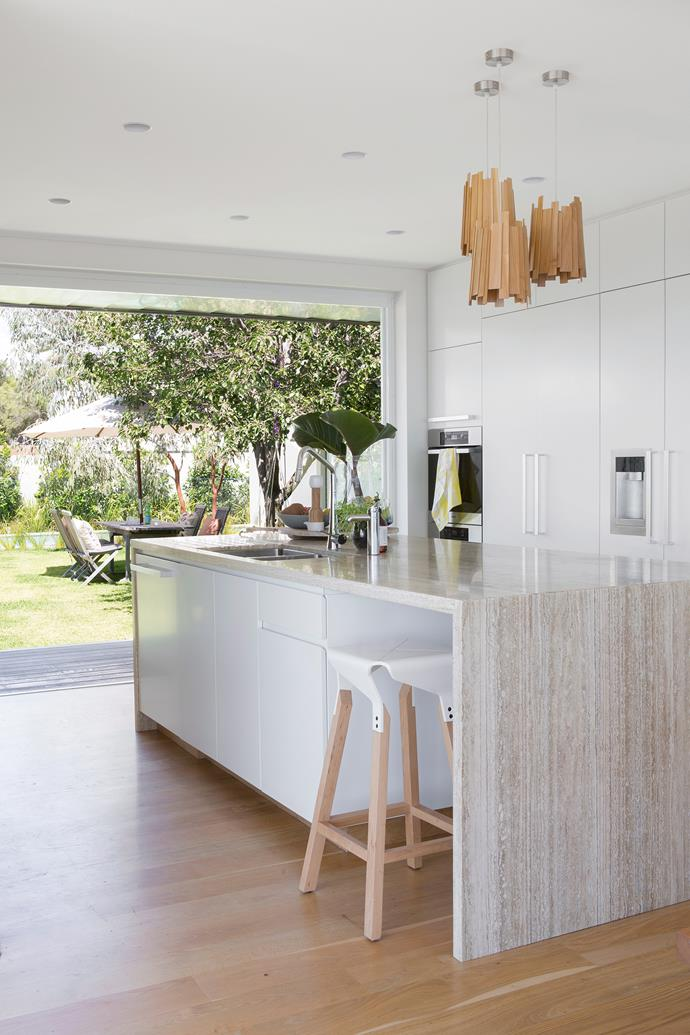 This stunning Scandi-style kitchen brings the outdoors in by using wooden accents throughout. If you're going for a similar look, try using a timber laminate on the benchtop as well as on the floor. Use different tones to provide contrast. Then sit at your island with an iced tea (or wine) and enjoy that view! *Photo: Angelita Bonetti / bauersyndication.com.au*