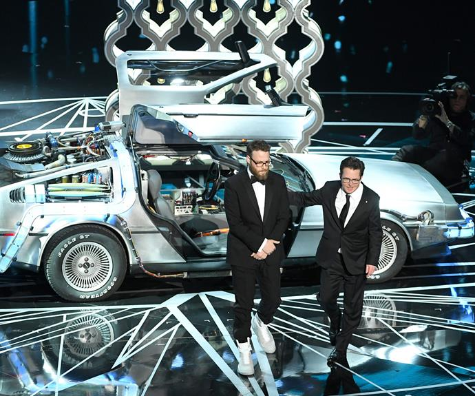 Seth Rogen and Michael J. Fox stand in front of a DeLorean in a nod to *Back To The Future*.