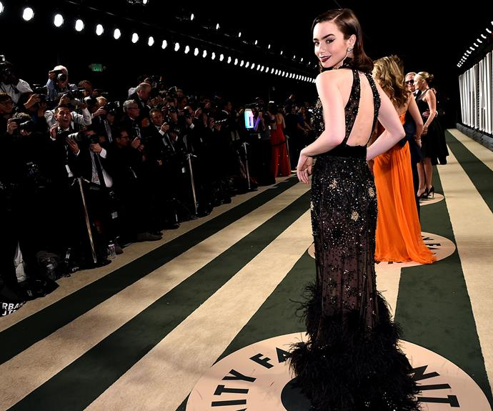 Lily Collins rises to the special occasion in a beaded and feathered gown.