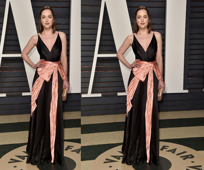 Dakota Johnson brightens up her black dress with a coral pink satin bow.