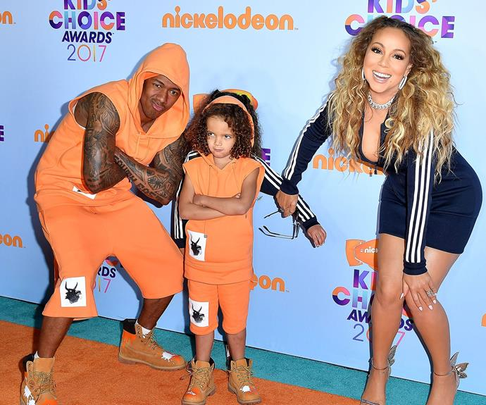 Monroe hides behind her twin brother on the orange carpet.