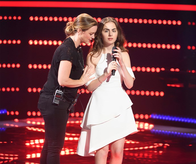 Lara is helped onto *The Voice* stage by a member of the crew.