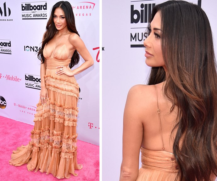 Nicole Scherzinger looks like an absolute goddess in the peach-coloured, tiered gown and flowing locks to boot.