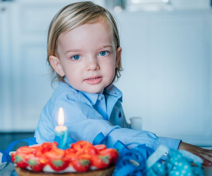 The young Prince is photographed here with a classic Swedish Midsummer birthday cake, covered in bright strawberries and a candle shaped in the number 2.