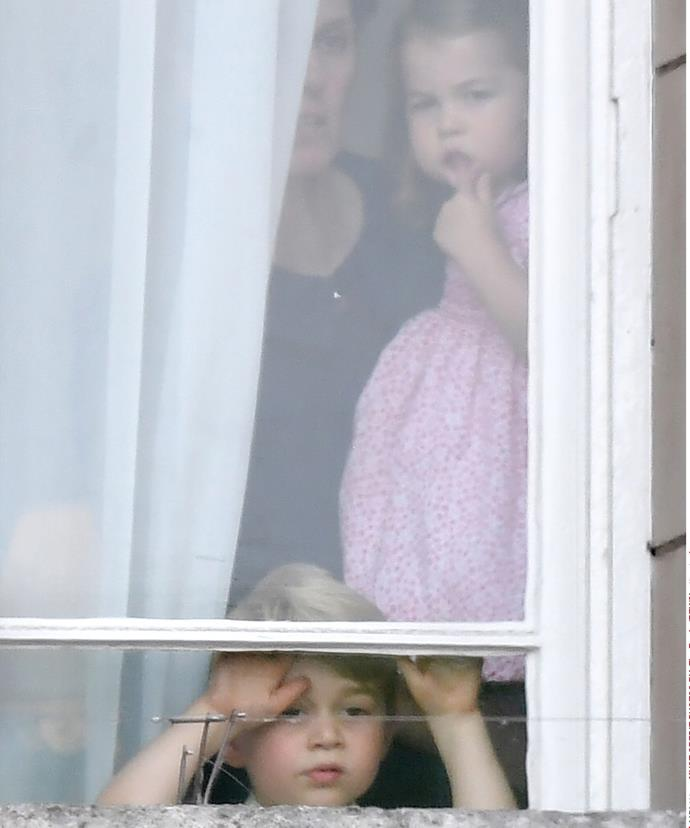 Peek-a-boo! Prince George and Princess Charlotte watch all the action of the parade from the window of Buckingham Palace.