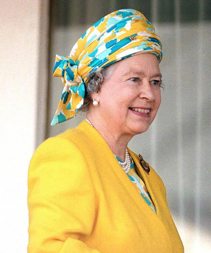 """In 1996 as she stepped out on the Royal Yacht, Queen Elizabeth opted for a gorgeous yellow and blue [turban-style piece](https://www.girlfriend.com.au/silk-scarf-fashion-trend