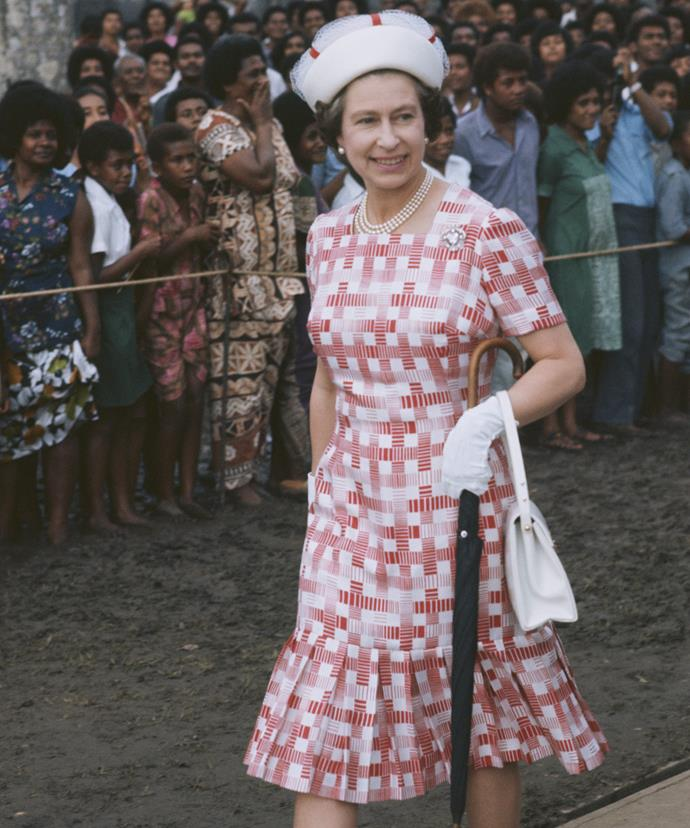 The pleated dress! The white gloves! The brolley! And of course the pill-box white hat! It's all so beautifully chic. The Queen works the crowds in Fiji, 1977.