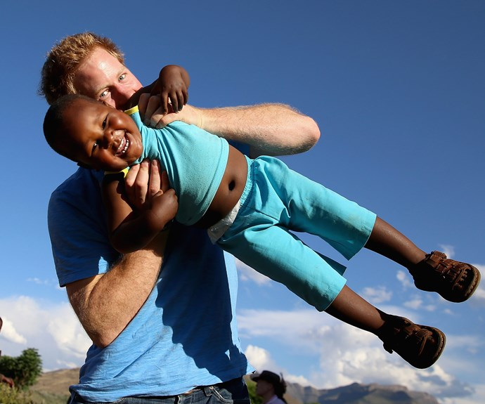 Harry swings around a little boy called Lerato during a visit to an orphanage in Lesotho, Africa.
