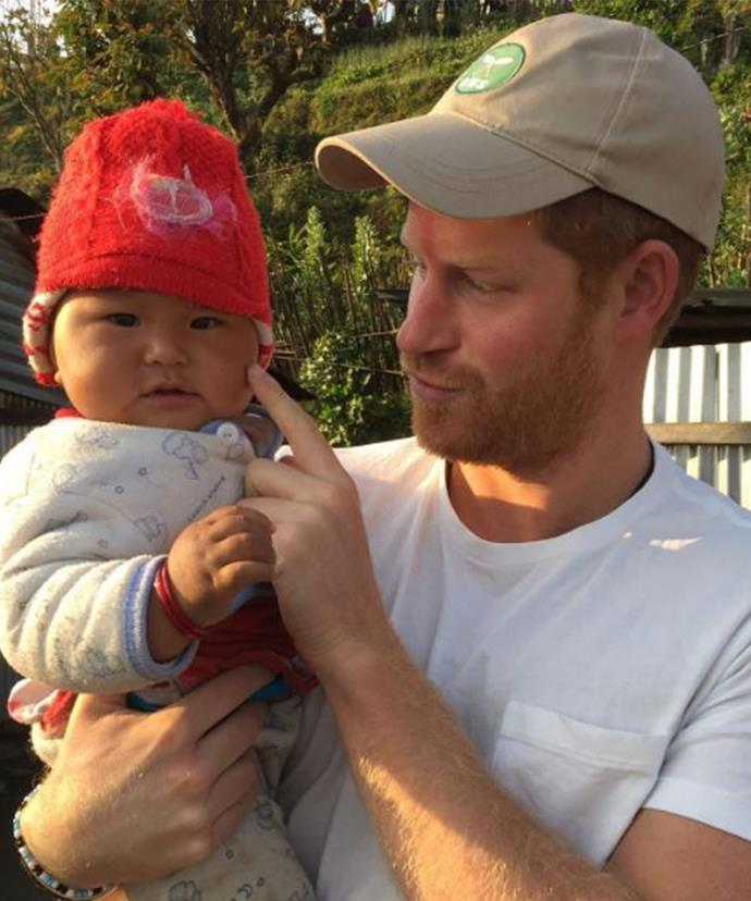 The Prince shares a tender moment with a chubby-cheeked baby in Nepal.