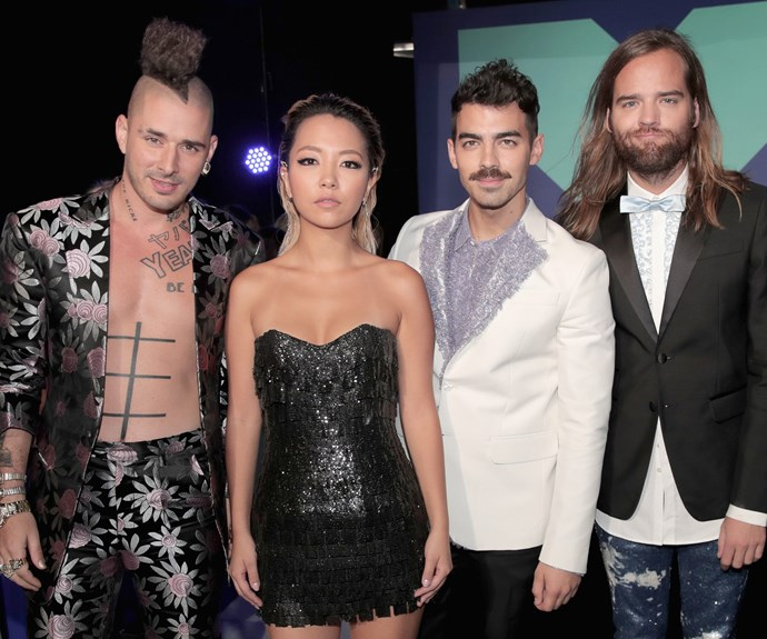 The singer, whose brother Nick Jonas famously dated Delta Goodrem, poses with his band DNCE.