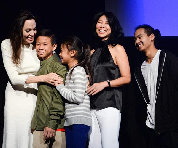Angelina, who was promoting her latest film *First They Killed My Father* at the film festival, cuddles up to actor Kimhak Mun, actress Sareum Srey Moch, executive producer and screenwriter Loung Ung and executive producer and her son Maddox Jolie-Pitt.