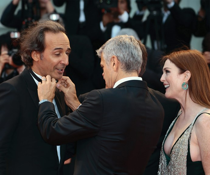 George casually fixes up Alexandre Desplat's bow tie.