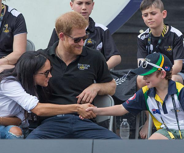 Meghan shakes a little boy's hand.