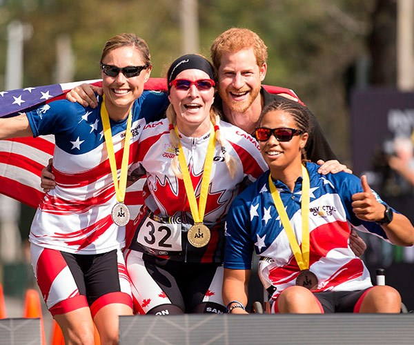 Prince Harry poses with medalists in the Women's Recumbent Bike IRECB1 time trial, (L-R) silver medalist Amy Dotson of the United States, gold medalist Julie Marcotte of Canada and bronze medalist Gabby Graves-Wake.
