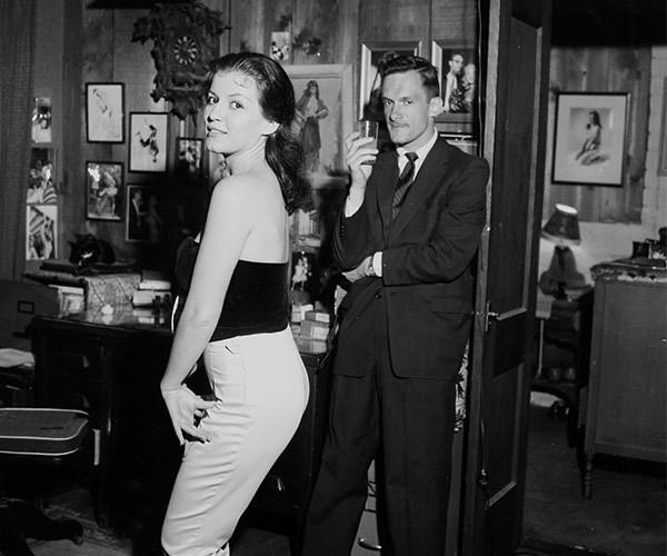 The dapper entrepreneur enjoys a stiff drink in the company of a very pretty woman at a Playboy shindig in LA in 1957.