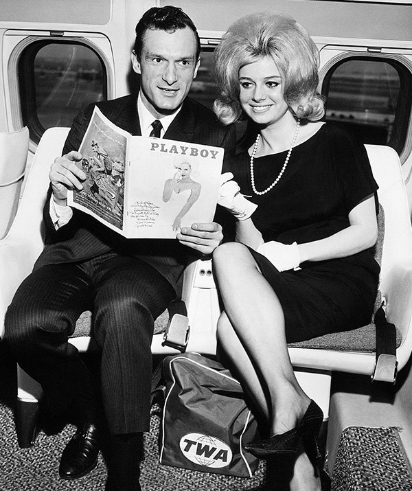 The editor and his cover girl! Hef cuddles up to Cynthia Maddox on a super-jet in Chicago in 1962. She's also gracing the mag's February edition in his hands.