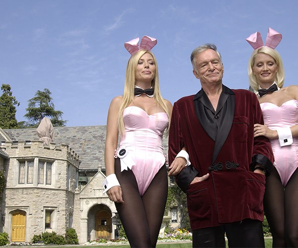 "Flanked by two iconic bunnies, including former girlfriend **Holly Madison**, the trio film a scene at the Playboy mansion for a video game commercial in 2003. ""I have about 100 pairs of pyjamas. I like to see people dressed comfortably,"" he's said of his quirky get up."