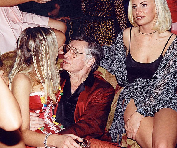 You can tell it's the '90s thanks to those over-sized specs! The father-of-four puckers up to kiss a pretty blonde at yet another party at the mansion in 1998.