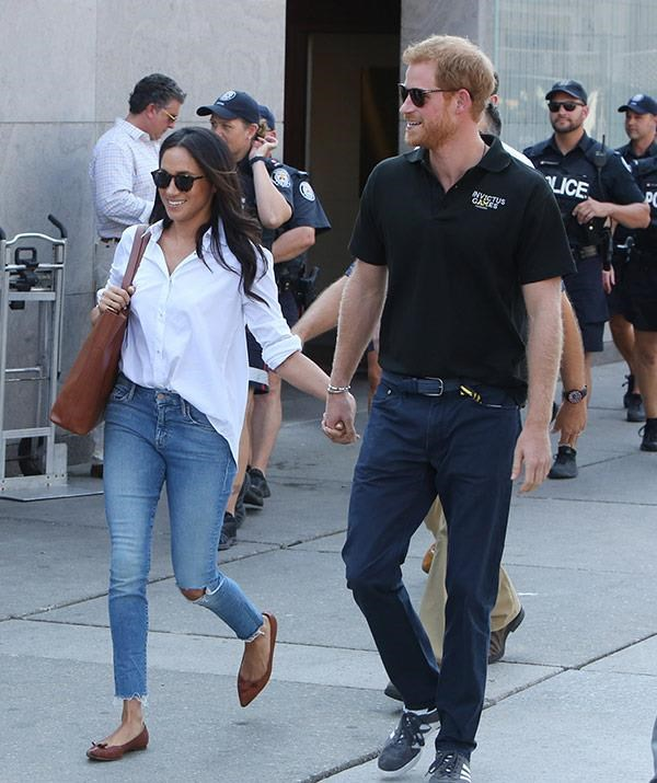 "Classic off-duty style. For her first ""official"" outing with beau Prince Harry, Meghan wore an over-sized white shirt, nipped in at the front with a perfect tuck into a pair of cropped at the ankle jeans. Don't think we didn't notice that very un-royal rip at the knee and frayed hems - she's not a princess yet, so she can do what she wants."