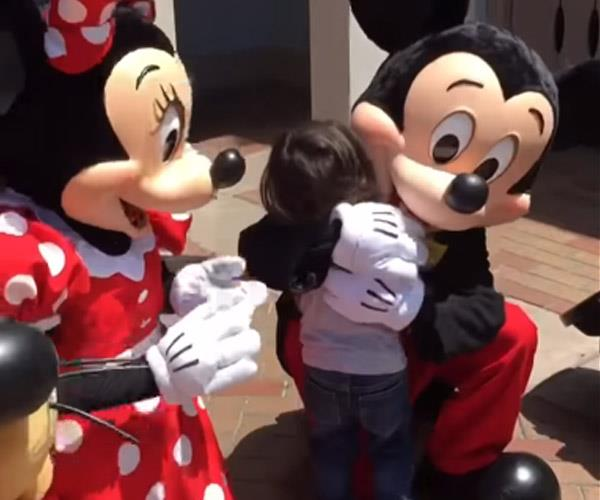 Overjoyed by the interaction, the toddler rushed to hug Minnie and then Mickey.