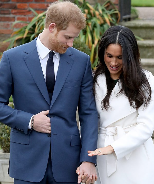Meghan takes a moment to show off her engagement ring, which Prince Harry designed.