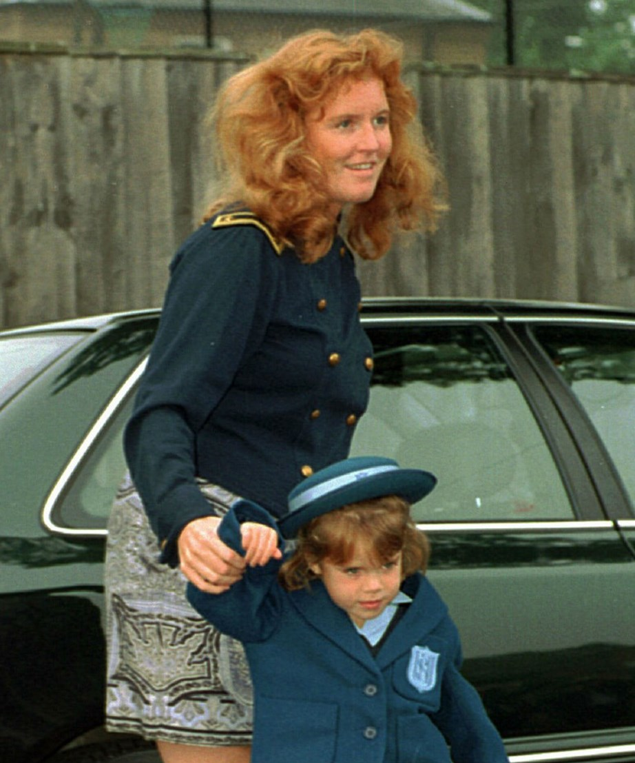 Looking as cute as a button in her school uniform, Princess Eugenie makes her way to her first day of school with her mum Fergie, in 1994. The Princess attended Upton House School in Windsor, where her older sister also attended. *(Image: Getty)*