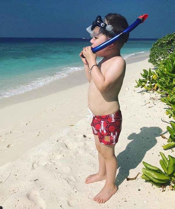 """Penning, """"Bout to go find some reef sharks! JK he refuses to go in the ocean and was back in a long-sleeve rashie, legionnaire hat and shaded pool two minutes after this photo."""""""