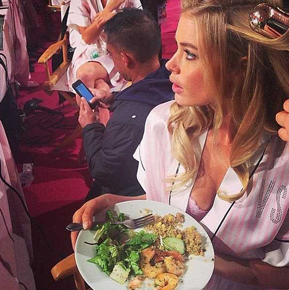 Victoria's Secret angel and mum Doutzen Kroes tucks in to food backstage at the show.