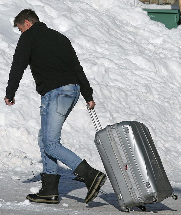 The reality star was flustered as he lugged his suitcase up the hill.