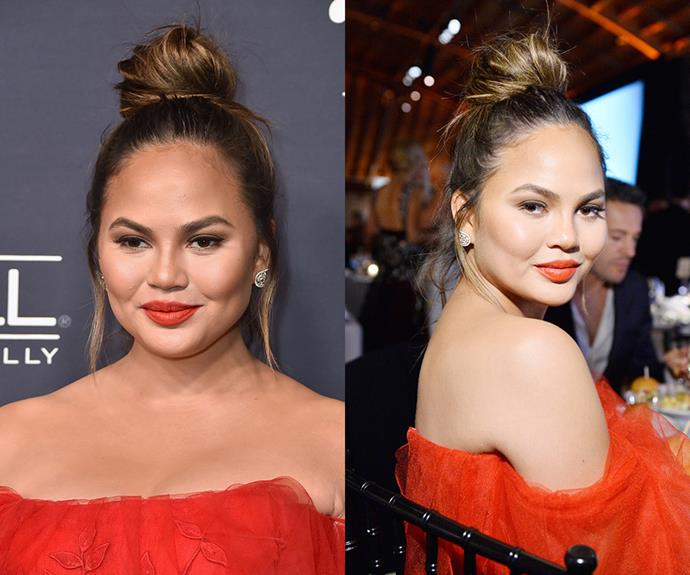 """**Chrissy Teigen's** playful top knot is a chic option for balmy nights out when it's too hot to deal with hot styling tools. (It's also a great way to disguise unwashed hair!). Start by pulling hair into a high pony at the crown and secure with an elastic. If working with clean hair, spritz a texturising spray through the lengths to give your bun that mussed-up sexiness and loosely twirl it out to create your top knot. Pin into place and """"pull"""" the bun with your fingertips to make the bun bigger and less perfect. Voilà, you're done! Though we highly recommend a slick of bright lipstick like Chrissy."""