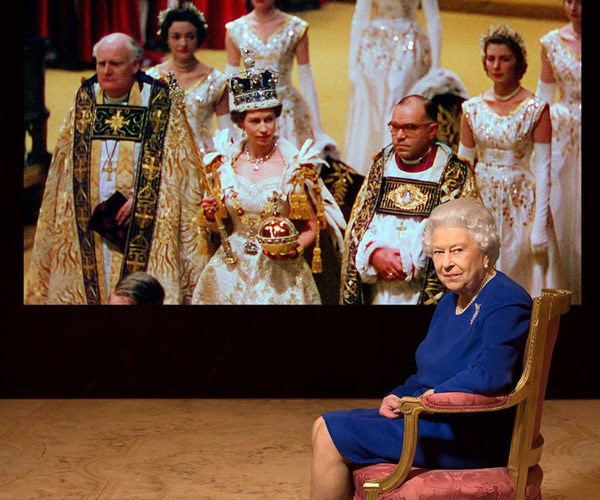 Queen Elizabeth poses in front of an image from her coronation.