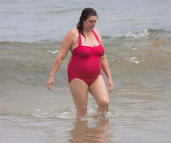 The reality star splashes about in the water.