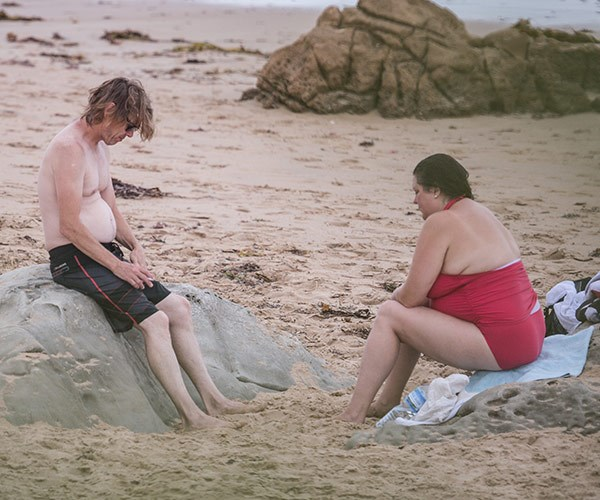 The couple relaxed on the sand after their surf.
