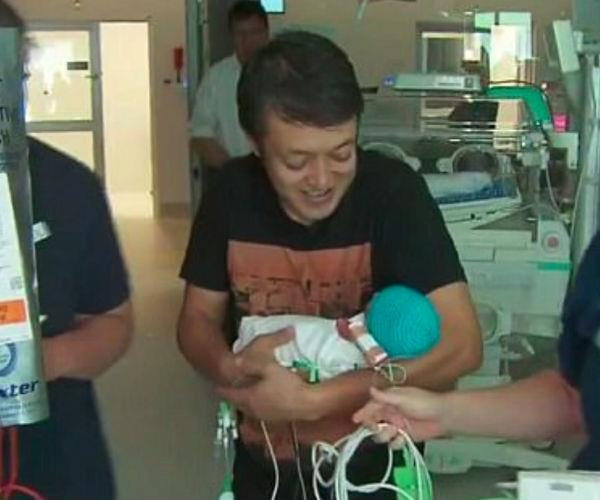 The proud new dad lovingly cradles one of four healthy baby boys. Image via *9News*.