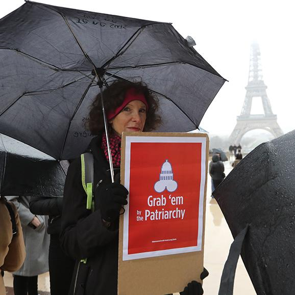 The movement is global! A woman stands defiantly in front of Paris' iconic Eiffel tower.