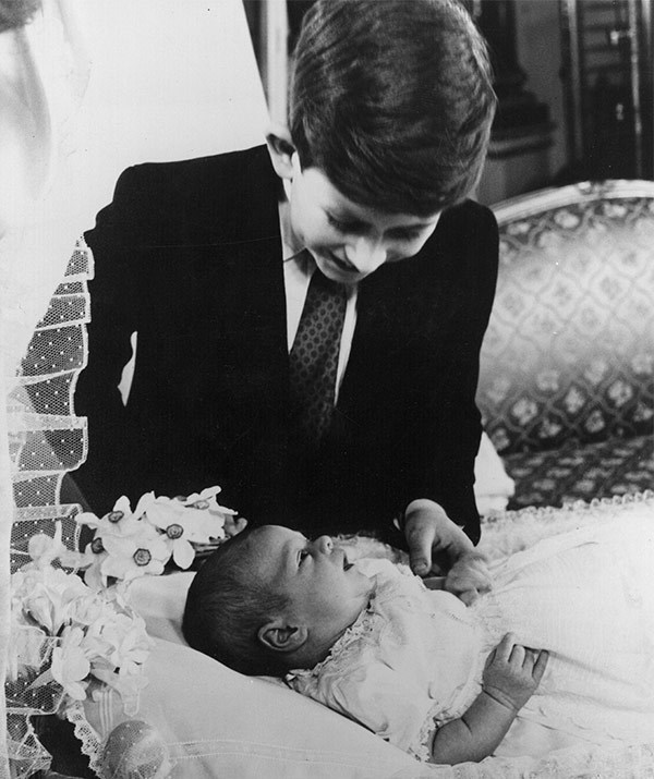 A young Prince Charles marvels at his little brother, Prince Andrew, in 1960.