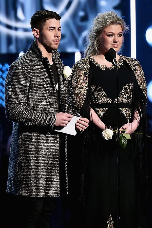 Nick Jonas and Kelly Clarkson take to the stage to present an award.
