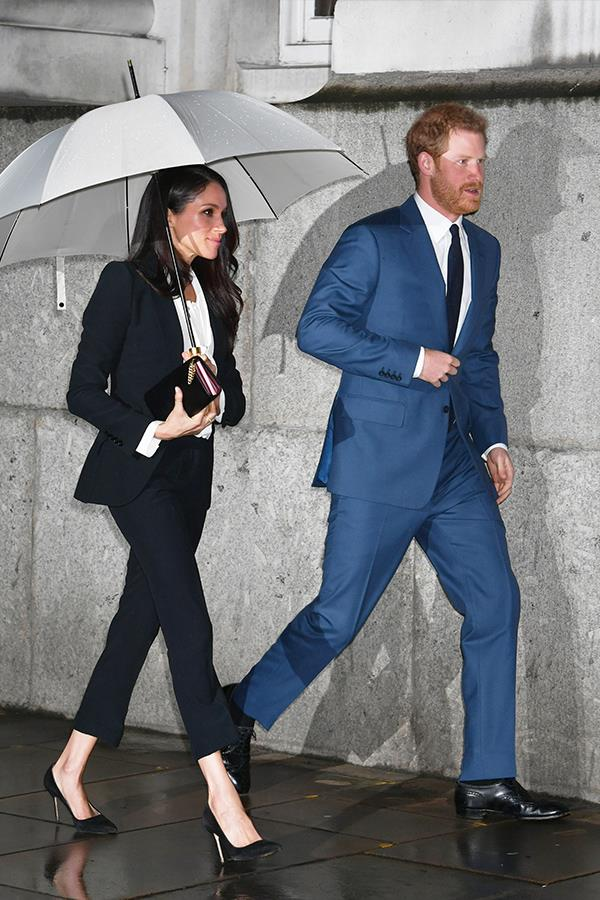 Harry and Meghan cut a stylish figure as they walk through the rain.