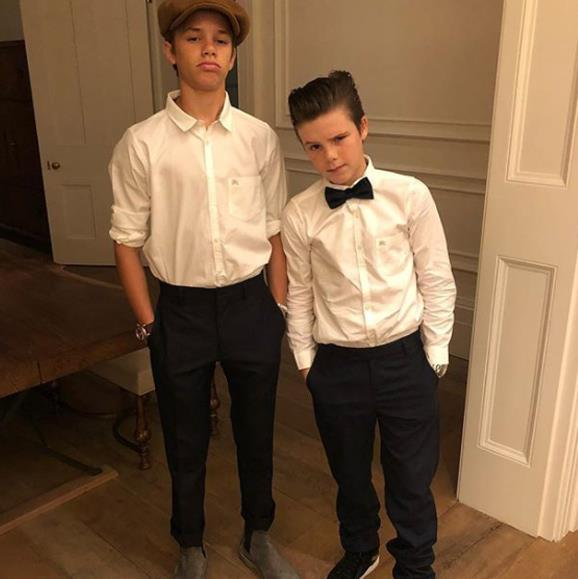 So suave! Young Beckhams Romeo and Cruz follow in their fashionable parents' footsteps as they accessorise matching white shirts and black trousers with their own stylish flare.