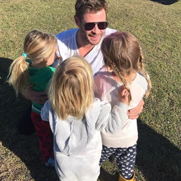 "India and twins Sasha and Tristan smother dad Chris in cuddles on his return home. ""Papa is back!!"" The tiny clans' mum captioned the cute pic."