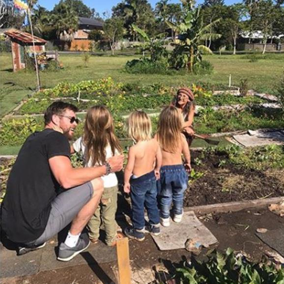 They're a down-to-earth family. Chris brushes the kids up on some gardening skills.