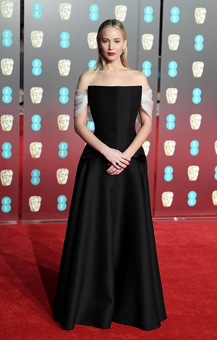 Jennifer Lawrence opts for a classic black gown with a shawl detail.
