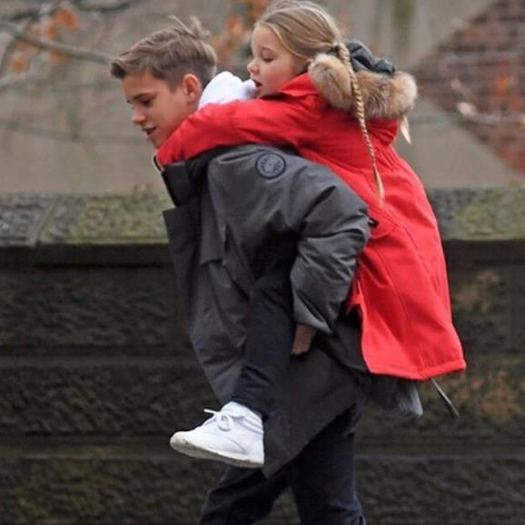 Second-oldest Beckham child Romeo, sweetly gives his little sister a break from walking. What a lovely brother!